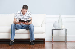 Man Reading on Living Room Couch Royalty Free Stock Photo