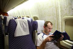 Man reading the magazine. On an airplane royalty free stock images
