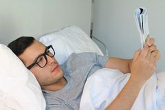 Man reading a magazine in bed royalty free stock images