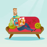 Man reading a magazine on the couch. Stock Photo