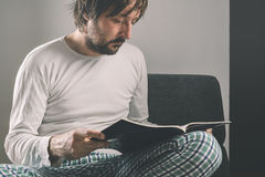 Man reading magazine early in the morning, wearing pajamas Stock Photo
