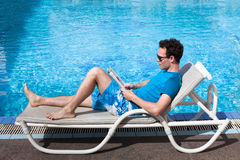 Man reading magazine near swimming pool Royalty Free Stock Image