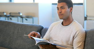 Man reading a magazine in a waiting room stock footage