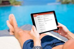 Man reading mail on tablet while on vacation stock photography