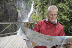 Man Reading Map Against Waterfall Royalty Free Stock Photo
