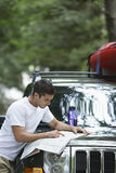 Man Reading Map On Car Bonnet Stock Photography