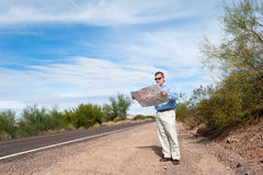 Man reading map on deserted road Stock Photography