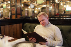 Man reading menu. The mid adult man reading a menu at the restaurant Stock Photo