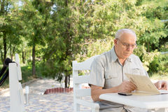 Man reading a menu at an open-air cafe Royalty Free Stock Image