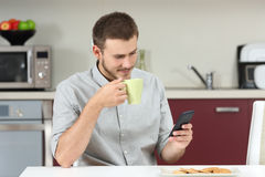 Man reading message on phone at breakfast Stock Image