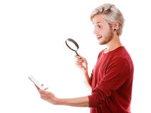 Man reading message on phone using loupe Royalty Free Stock Photography
