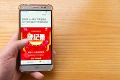 Man reading mobile news saying JD.COM sales 127.1-billion RMB from November 1 to 11 royalty free stock photos