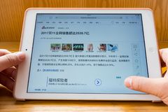 Man reading mobile news saying the total online sales is 253.97-billion RMB on the Chinese online shopping day of November 11. Zhongshan,China-November 12,2017 stock photos