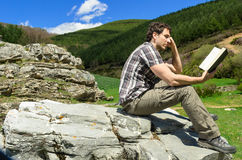 Man reading in nature. Man reading and enjoying a book in natural landscape Royalty Free Stock Photo