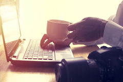 Man is reading news on laptop and drinking hot coffee. Stock Image