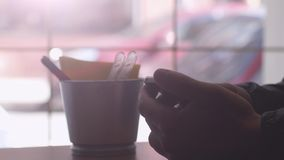 Man reading news with mobile phone and drinks coffee by the window in cafe. 3840x2160. Man reading news with mobile phone and drinks coffee by the window stock footage