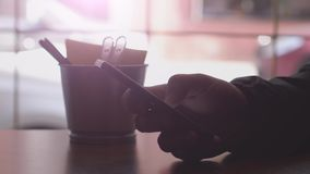 Close up of men hands use mobile phone and drinks coffee by the window in cafe. 3840x2160. Man reading news with mobile phone and drinks coffee by the window stock footage