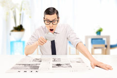 Man reading the news with scrutiny in an office. Surprised man reading the news with scrutiny in an office Stock Images