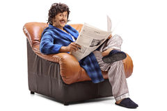 Man reading the news seated in an armchair. Young man reading a newspaper seated in a comfortable armchair isolated on white background Stock Photos