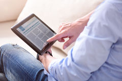 Man reading news on tablet Stock Photography
