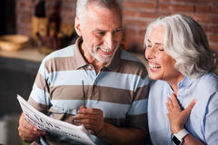 Man reading the news and woman laughing Royalty Free Stock Image