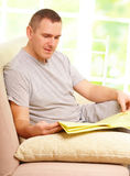 Man reading newspaper. Hansome man reading newspaper, sitting on couch at home and gently smiling Stock Photos