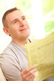 Man reading newspaper. Handsome man reading newspaper, sitting on couch at home and smiling Stock Photos