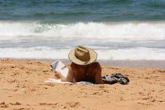 Man reading newspaper. On a sandy beac Stock Photos