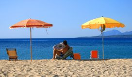 Man reading newspaper on beach Stock Images