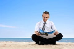 Man reading newspaper on the beach Royalty Free Stock Images