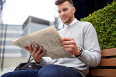Man reading newspaper on city street bench Stock Image