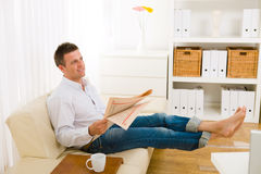 Man reading newspaper on couch Stock Photography