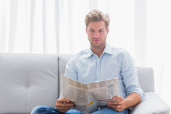 Man reading a newspaper on a couch Royalty Free Stock Images