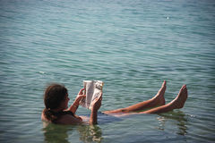 Man reading a newspaper in Dead Sea stock photos