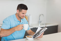 Man reading newspaper while drinking coffee Stock Image