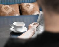 A man reading newspaper and drinking coffee sitting in cafe or at home in kitchen at morning time. A coffee cup on dark blue table royalty free stock photo