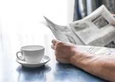 A man reading newspaper and drinking coffee sitting in cafe or at home next to kitchen window at sunny morning time. A Stock Photo