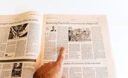 Man reading newspaper Financial Times about hurricane maria deva