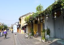 A man reading newspaper in front of a closed shop early sunny morning in Hoi An stock photos