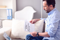 Man reading newspaper in front of laptop. What is new. Serious mature bearded man reading a broadsheet while sitting in front of the laptop with diagrams on the Stock Photography