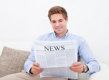 Man Reading Newspaper. Happy Young Man Sitting On Couch Reading Newspaper Stock Images