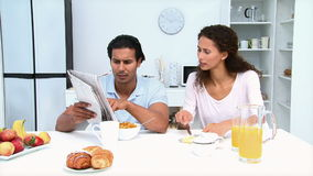 Man reading newspaper while having breakfast with his girlfriend stock video footage