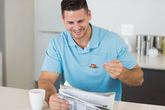 Man reading newspaper while having breakfast at table Royalty Free Stock Image