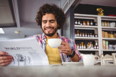 Man reading newspaper while having coffee Stock Photo
