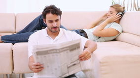 Man reading a newspaper and his girlfriend listens to music Stock Photos