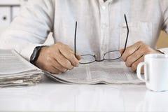 Man reading newspaper and holding eyeglasses Stock Image