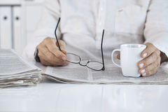 Man reading newspaper and holding eyeglasses Royalty Free Stock Photos