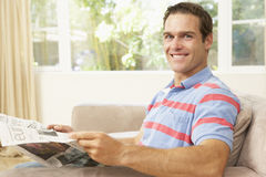 Man Reading Newspaper At Home Stock Photo