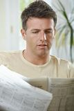 Man reading newspaper at home Stock Image