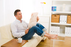 Man reading newspaper at home Stock Photography